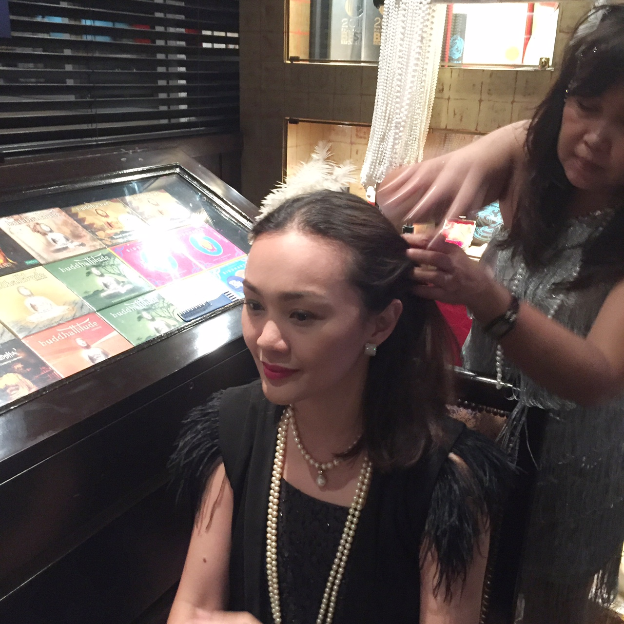 At the party they had a makeshift parlour where the ladies could choose from a wide array of headpieces, strands of imitation pearls and feather boas, all cleverly sourced from Divisoria. Here I am getting my hair done by the stylist.